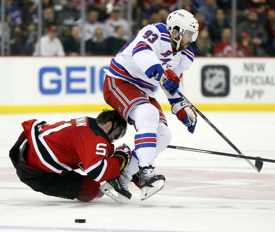 New Jersey Devils center Sergey Kalinin, left, of Russia, gets his helmet knocked off during contact with New York Rangers defenseman Keith Yandle during the second period of an NHL hockey game, Tuesday, Feb. 2, 2016, in Newark, N.J. (AP Photo/Julio Cortez)