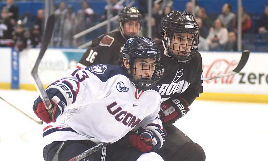 Hour photo/John Nash - UConn's Joseph Masonius, left, and Brown's Alex Brink watch a play develop in front of them during Tuesday's non-conference college hockey game at the XL Center in Hartford.