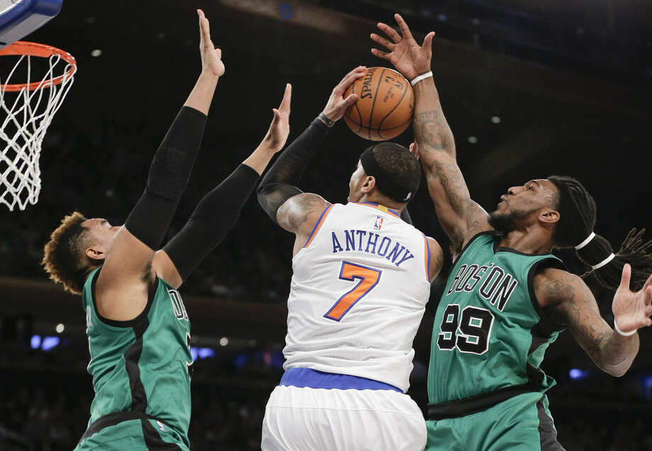 New York Knicks forward Carmelo Anthony (7) is double teamed while shooting against Boston Celtics center Jared Sullinger, left, and forward Jae Crowder (99) during the first quarter of an NBA basketball game, Tuesday, Feb. 2, 2016, in New York. (AP Photo/Julie Jacobson)