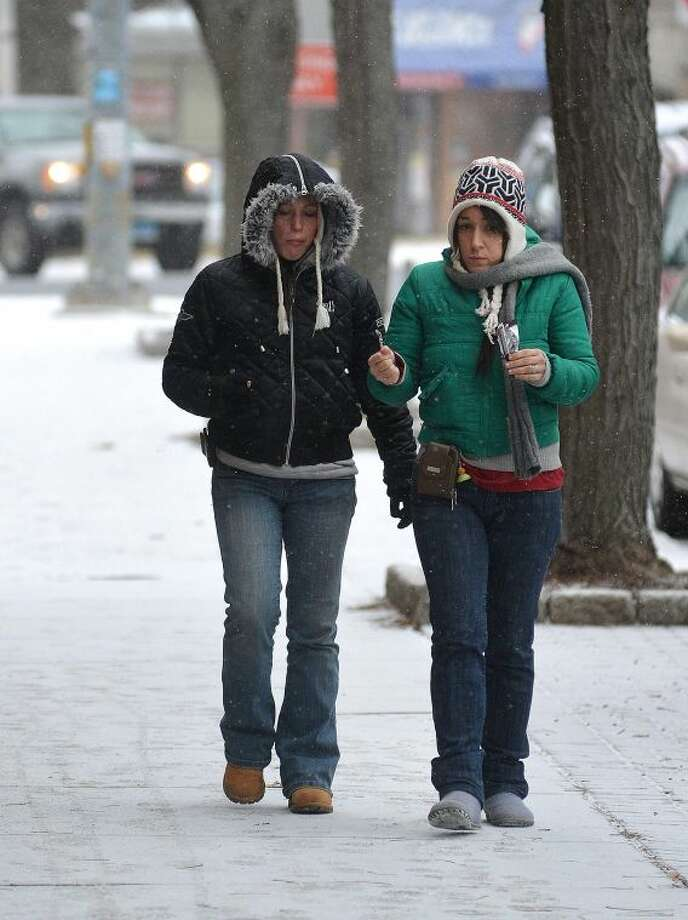 Hour Photo/Alex von Kleydorff Amanda Berquist and Victoria Nirschel share a chocolate bar as they walk on Mott ave as snow starts to fall in Norwalk on Tuesday morning