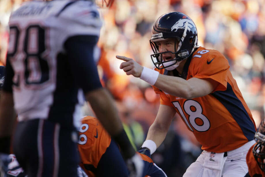 Denver Broncos quarterback Peyton Manning (18) calls out a play during the second half of the AFC Championship NFL playoff football game against the New England Patriots in Denver, Sunday, Jan. 19, 2014. (AP Photo/Charlie Riedel)