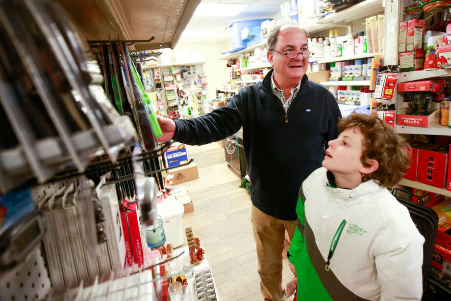 Hour photo/Chris Palermo Yves Berliet and his son Charlotte pick up some supplies for the upcoming snow storm at Rowayton Hardware Sunday night.