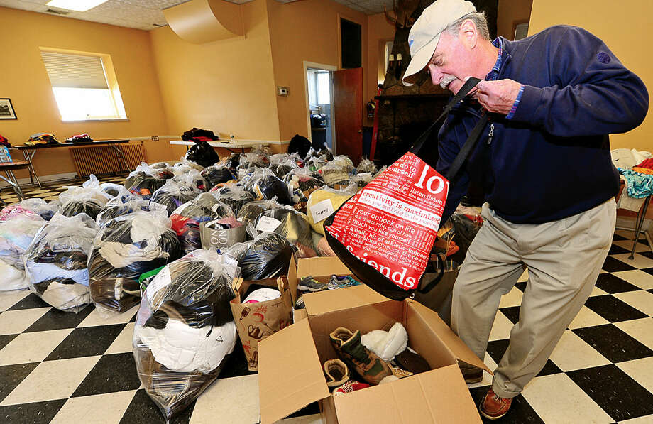 """Hour photo / Erik Trautmann Volunteer David Lindsay sorts outerwear during The Rowayton Community Association's first annual winter """"Bundle Up Rowayton"""" clothing drive Saturday at the Rowayton Community Center to benefit the Open Door Shelter in South Norwalk."""