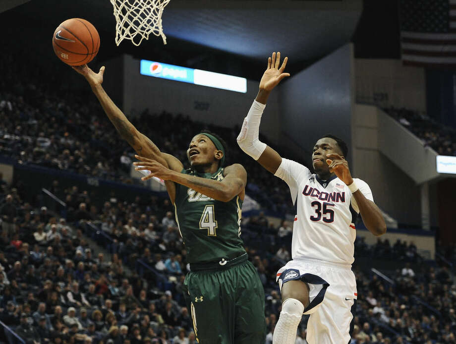 South Florida's Corey Allen Jr., left, shoots as Connecticut's Amida Brimah defends during the second half of an NCAA college basketball game, Sunday, Jan. 25, 2015, in Hartford, Conn. UConn won 66-53. (AP Photo/Jessica Hill)