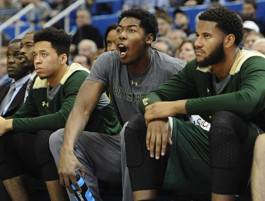 South Florida's Chris Perry, center, cheers his team from the bench during the second half of an NCAA college basketball game against Connecticut, Sunday, Jan. 25, 2015, in Hartford, Conn. Perry, a starting forward for USF, was hospitalized last night with chest pains and sat out the game. (AP Photo/Jessica Hill)