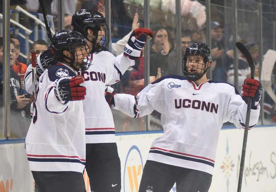 Hour photo/John Nash - UConn's Spencer Naas, left, celebrates his first period goal with Husky teammates during Tuesday's non-conference college hockey game at the XL Center in Hartford.