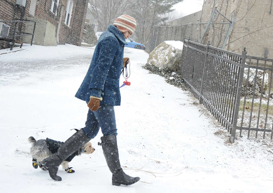 A pedestrian braves the cold Tuesday along West Avenue in Norwalk as steady snow falls across the area. Hour photo/Matthew Vinci