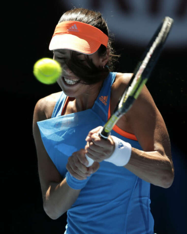 Ana Ivanovic of Serbia makes a backhand return to Eugenie Bouchard of Canada during their quarterfinal at the Australian Open tennis championship in Melbourne, Australia, Tuesday, Jan. 21, 2014.(AP Photo/Rick Rycroft)