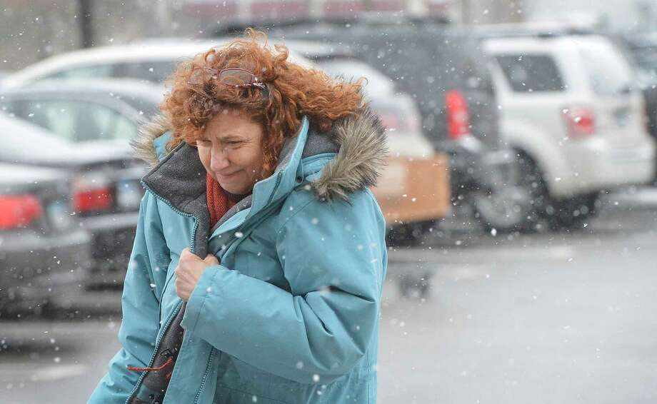 Hour Photo/Alex von Kleydorff Melissa Dunsmore braces against the snow and wind as she runs some last minute errands in Norwalk Monday afternoon