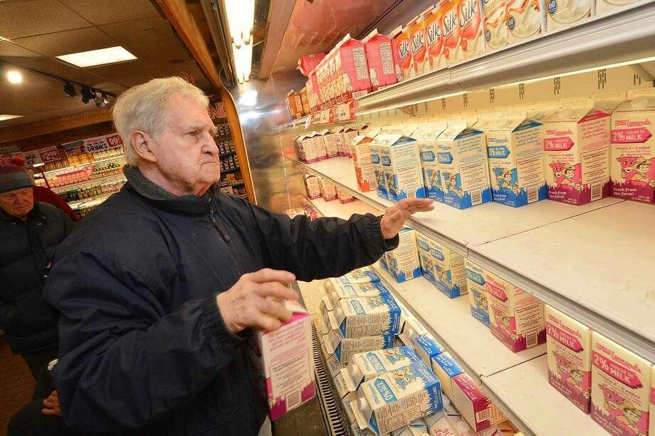 Hour Photo/Alex von Kleydorff Harrington Oberlander picks up a half dozen containers of milk at Stew Leonard's Monday in preparation for Winter Storm Juno