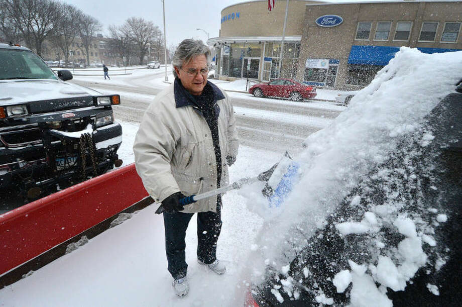 Hour Photo/Alex von Kleydorff Carl DelSpinta clears the snow off his car on Main st in Norwalk Tuesday, as a steady snow falls on the area