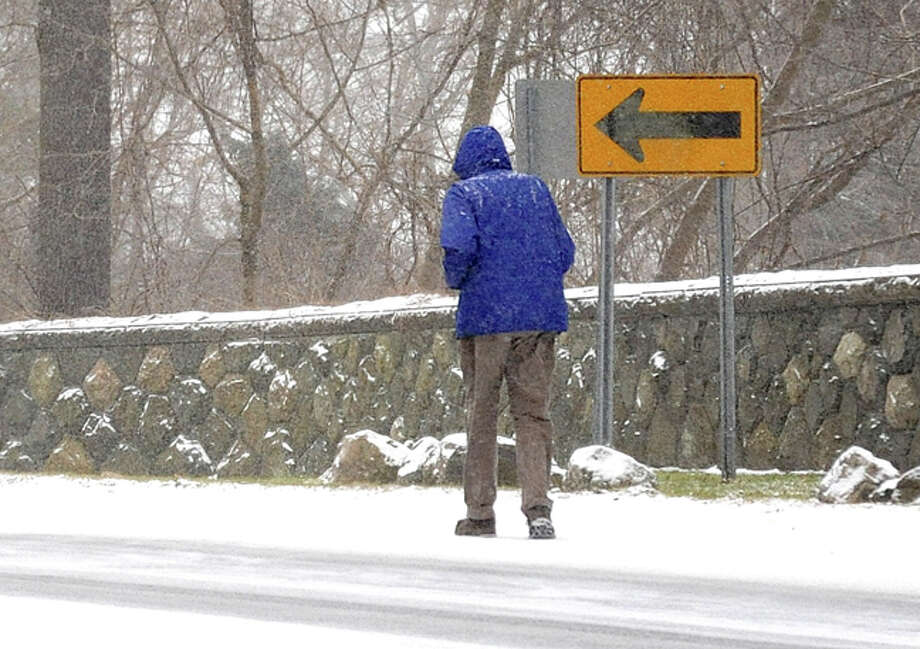 A pedestrian makes his way down Rowayton Avenue in Norwalk Tuesday afternoon as steady snow falls across the area. Hour photo/Matthew Vinci
