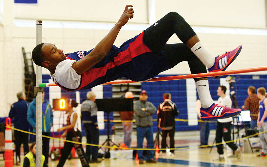 Hour photo / Erik Trautmann Brien McMahon High School's Dennison Najeem competes in the high jump during the FCIAC Eastern Division championship track meet at Wilton High School Saturday.