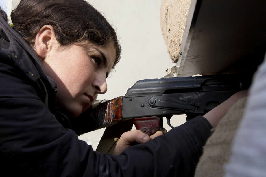 In this Wednesday, Nov. 19, 2014 photo, a female Kurdish fighter takes aim in Kobani, Syria. Kurdish fighters backed by intense U.S.-led airstrikes pushed the Islamic State group almost entirely out of the Syrian town of Kobani on Monday, Jan. 26, 2015, marking a major loss for extremists whose hopes for easy victory dissolved into a bloody, costly siege that seems close to ending in defeat. (AP Photo/Jake Simkin, File)
