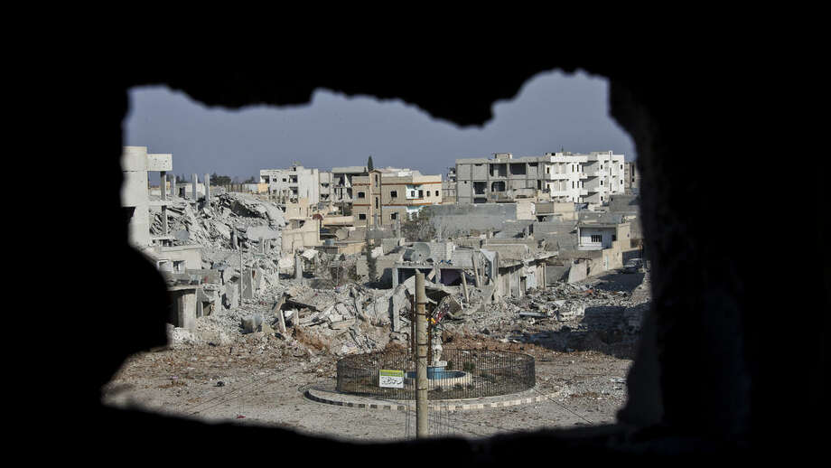 FILE - This Nov. 20, 2014 file photo shows an area controlled by the Islamic State group, past the Qada Azadi roundabout, foreground, in Kobani, Syria. Kurdish fighters backed by intense U.S.-led airstrikes pushed the Islamic State group almost entirely out of the Syrian town of Kobani on Monday, Jan. 26, 2015, marking a major loss for extremists whose hopes for easy victory dissolved into a bloody, costly siege that seems close to ending in defeat. (AP Photo/Jake Simkin, File)