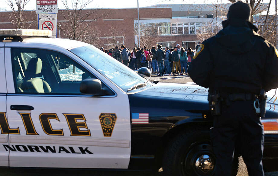 Hour photo / Erik Trautmann Norwalk police watch over an evacuatuon drill at Brien Mcmahon High School Thursday morning.