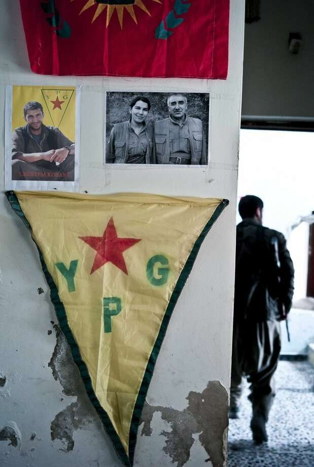 FILE - In this Nov. 2, 2014 photo, pictures adorn the walls of a position held by Kurdish popular protection (YPG) and women's defense (YPJ) units of fighters who have been lost in the battles against the Islamic State group in Kobani, Syria. Kurdish fighters backed by intense U.S.-led airstrikes pushed the Islamic State group almost entirely out of the Syrian town of Kobani on Monday, Jan. 26, 2015, marking a major loss for extremists whose hopes for easy victory dissolved into a bloody, costly siege that seems close to ending in defeat. (AP Photo/Jake Simkin, File)