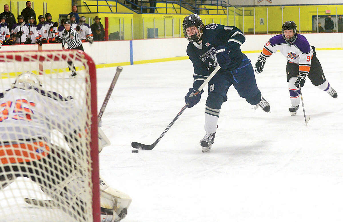 Samuel New of the Staples-Weston co-op hockey team takes a shot on he Stamford High School-Westhill co-op team goal at Terry Connors Rink in Stamford Saturday night.