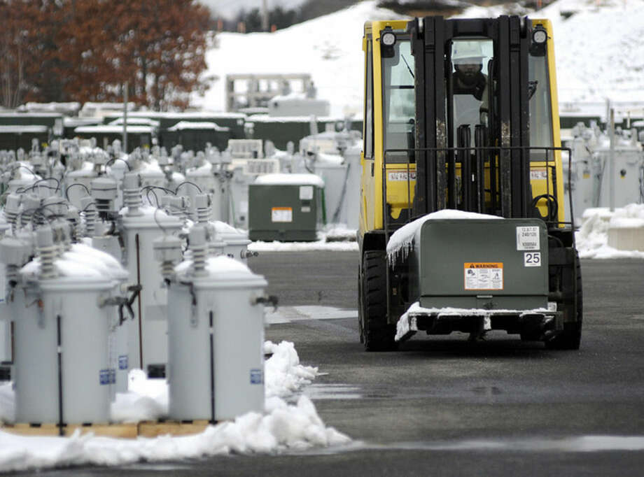 National Grid worker Justin Tervo moves transformers to a staging area at the company's Central Distribution Center in Whitinsville, Mass., Monday, Jan. 26, 2015, in preparation for a massive winter storm. New England is bracing for a blockbuster blizzard threatening more than 2 feet of snow, hurricane-force winds, coastal flooding and widespread power outages. (AP Photo/Worcester Telegram & Gazette, Rick Cinclair)