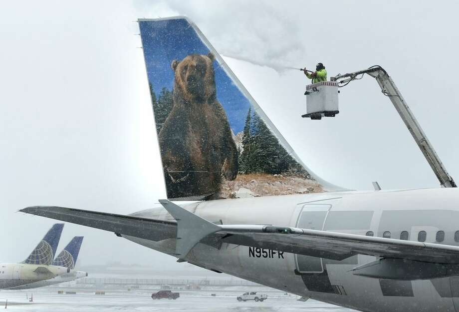 A crewmember de-ices a Frontier Airlines plane at LaGuardia Airport in New York, Monday, Jan. 26, 2015. More than 5,000 flights in and out of East Coast airports have been canceled as a major snowstorm packing up to three feet of snow barrels down on the region. (AP Photo/Seth Wenig)