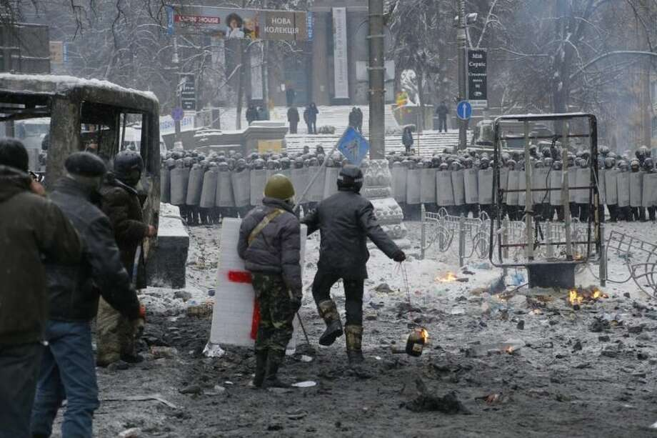 A protester, center, prepares to throw a Molotov cocktail during clashes with police in central Kiev, Ukraine, early Wednesday, Jan. 22, 2014. Two people have died in clashes between protesters and police in the Ukrainian capital Wednesday, according to medics on the site, in a development that will likely escalate Ukraine's two month-long political crisis. (AP Photo/Sergei Grits)
