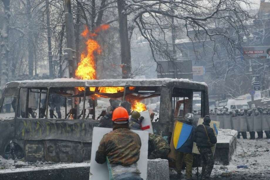 Protesters shield themselves behind a burned vehicle during clashes with police in central Kiev, Ukraine, early Wednesday, Jan. 22, 2014. Two people died in clashes between protesters and police in the Ukrainian capital Wednesday, according to medics on the site, a grim escalation of the country's two-month-long political crisis. (AP Photo/Sergei Grits)