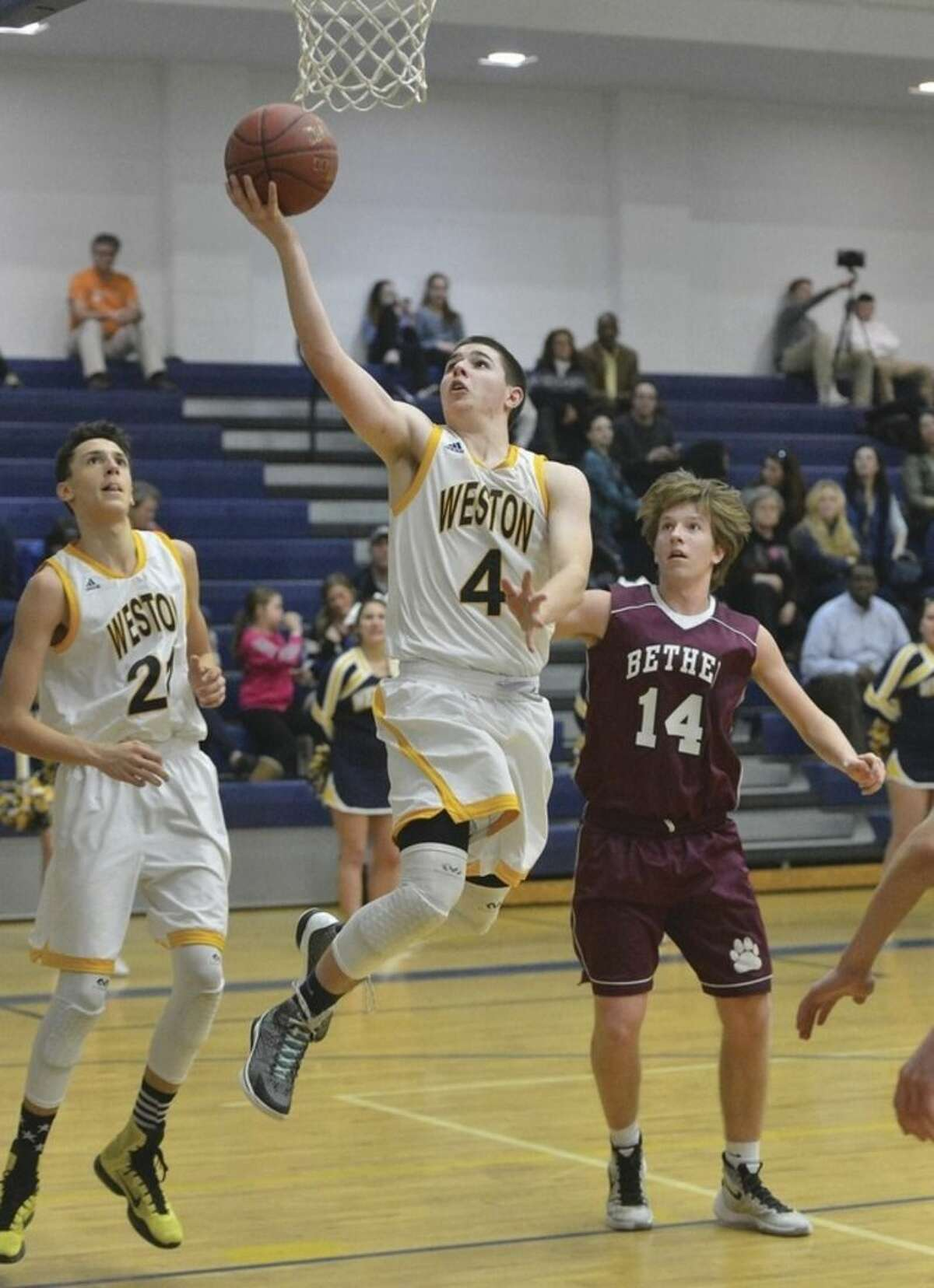 Hour photo/Alex von Kleydorff Weston's Andrew Folger (4) puts the ball in the hoop during Tuesday night's SWC encounter against Bethel.