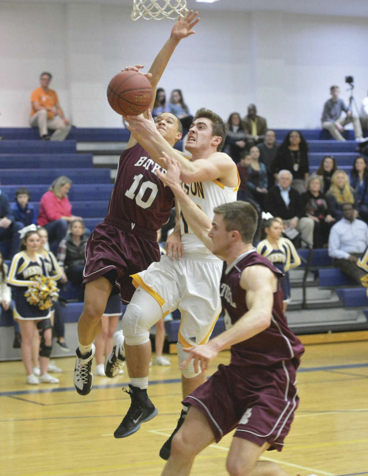 Weston's Jason Lawrence, center, tries to score between two Bethel defenders during Tuesday night's game at Weston High. The Trojans earned their second win of the season by defeating the Wildcats 49-39. Hour photo/ Alex von Kleydorff