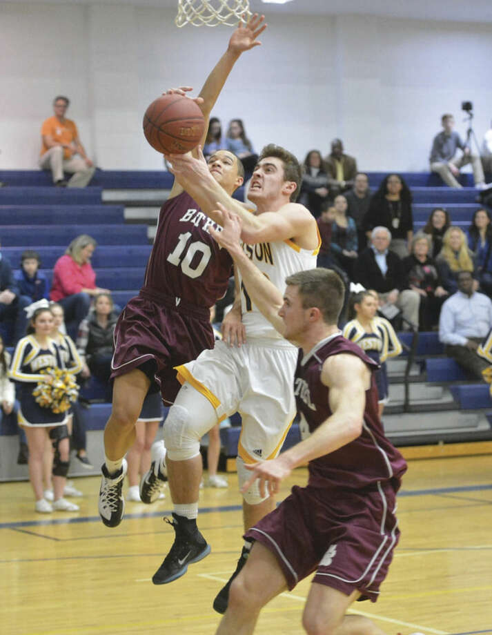 Weston's Jason Lawrence, center, tries to score between two Bethel defenders during Tuesday night's game at Weston High. The Trojans earned their second win of the season by defeating the Wildcats 49-39.Hour photo/Alex von Kleydorff