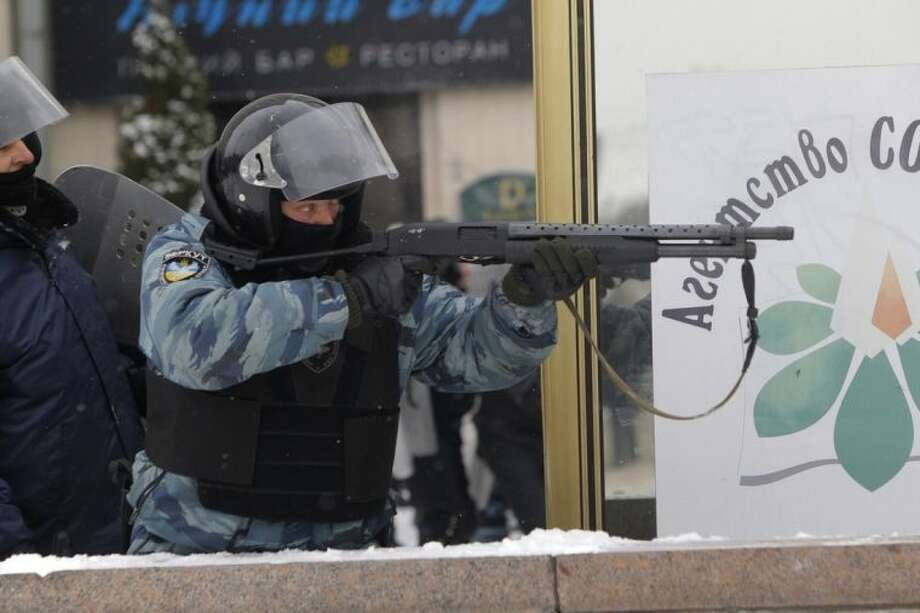 A police officer uses a shotgun during clashes with protesters in central Kiev, Ukraine, early Wednesday, Jan. 22, 2014. Police in Ukraine's capital on Wednesday tore down protester barricades and chased demonstrators away from the site of violent clashes, hours after two protesters died after being shot, the first violent deaths in protests that are likely to drastically escalate the political crisis that has gripped Ukraine since late November. (AP Photo/Sergei Grits)