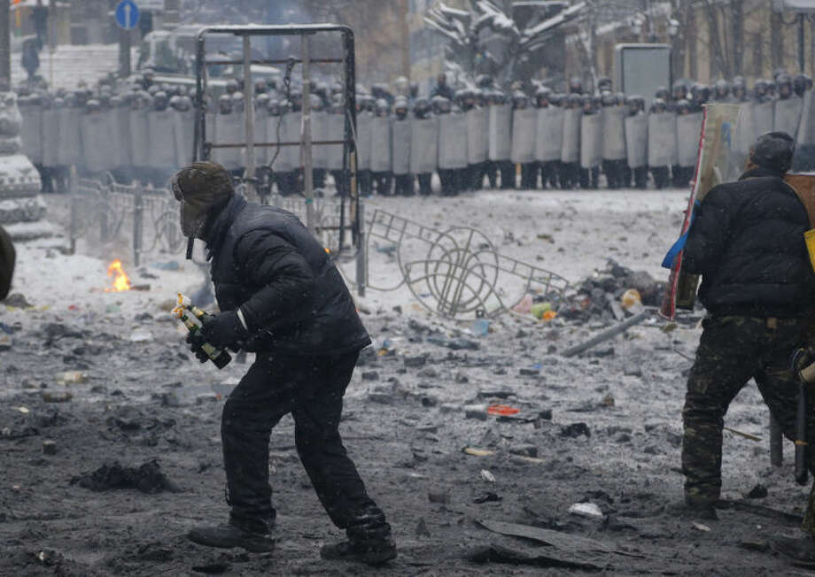 A protester, left, prepares to throw a Molotov cocktail during clashes with police in central Kiev, Ukraine, early Wednesday, Jan. 22, 2014. Two people have died in clashes between protesters and police in the Ukrainian capital Wednesday, according to medics on the site, in a development that will likely escalate Ukraine's two month-long political crisis. (AP Photo/Sergei Grits)