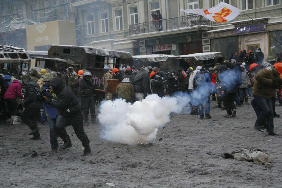 Protesters run away from a stun grenade as they clash with police in central Kiev, Ukraine, early Wednesday, Jan. 22, 2014. Two people have died in clashes between protesters and police in the Ukrainian capital Wednesday, according to medics on the site, in a development that will likely escalate Ukraine's two month-long political crisis. (AP Photo/Sergei Grits)