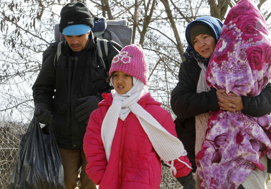 A family of refugees walks towards the border with Serbia from the transit center for refugees near northern Macedonian village of Tabanovce, Friday, Feb. 5, 2016. Macedonia accepts people only from war-affected zones who declare Austria or Germany as their final destination. (AP Photo/Boris Grdanoski)