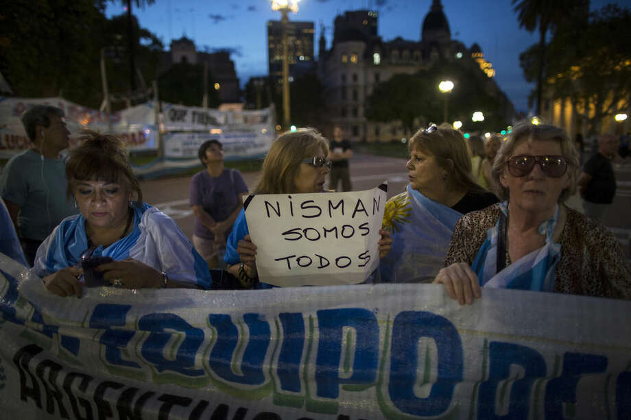 """A protester carries a sign that reads in Spanish """"We're all Nisman,"""" referring to the death of special prosecutor Alberto Nisman, in Plaza de Mayo square in Buenos Aires, Argentina, Monday, Jan. 26, 2015. Nisman was found dead Jan. 18 in his apartment, the day before he was scheduled to elaborate on explosive allegations that Fernandez shielded Iranian officials suspected in the largest terrorist attack in the South American country's history. (AP Photo/Ivan Fernandez)"""