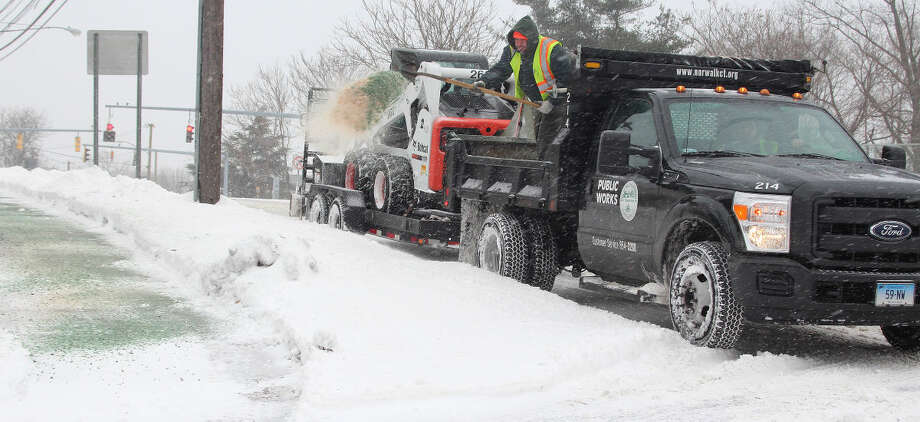 Hour photo/Chris Bosak Adrian Ibarrondo of the Norwalk Public Works throws salt to treat the sidewalks along East Avenue on Tuesday morning.