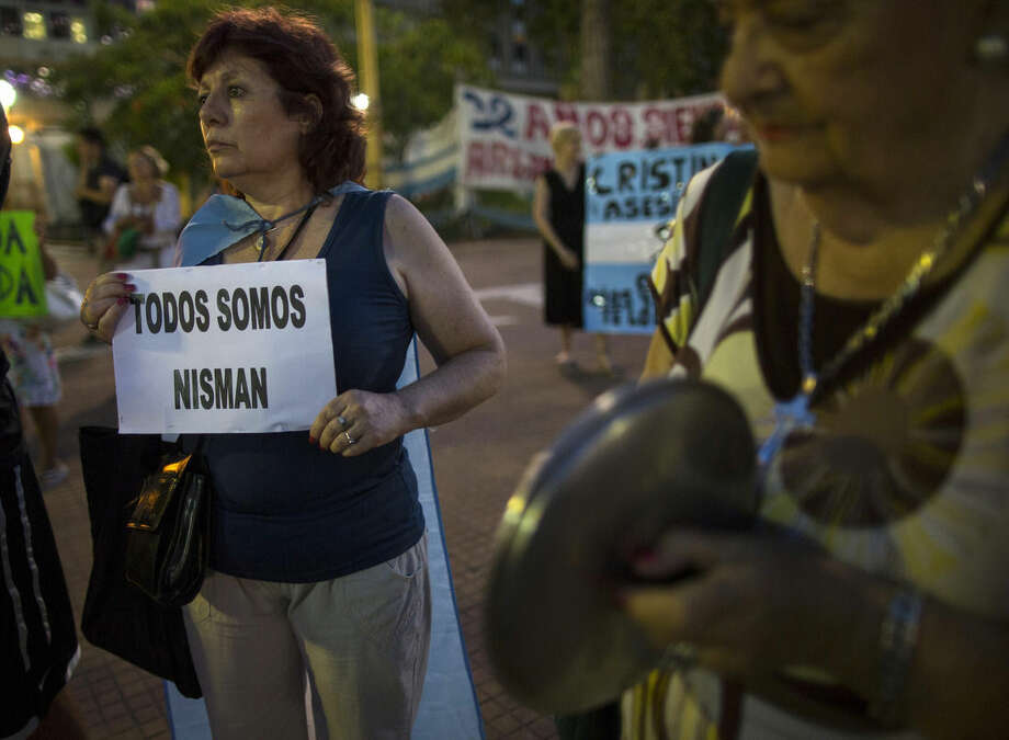 "A protester holds a sign that reads in Spanish ""We're all Nisman,"" referring to the death of special prosecutor Alberto Nisman, in Plaza de Mayo square in Buenos Aires, Argentina, Monday, Jan. 26, 2015. Nisman was found dead Jan. 18 in his apartment, the day before he was scheduled to elaborate on explosive allegations that Fernandez shielded Iranian officials suspected in the largest terrorist attack in the South American country's history. (AP Photo/Ivan Fernandez)"