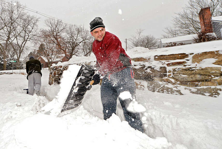 Hour photo / Erik Trautmann Tom Zadrima shovels the sidewalk at his sister's home on Saxon and Strawberry Hill Ave as Norwalkers cope with the blizzard that hit the Northeast Tuesday.