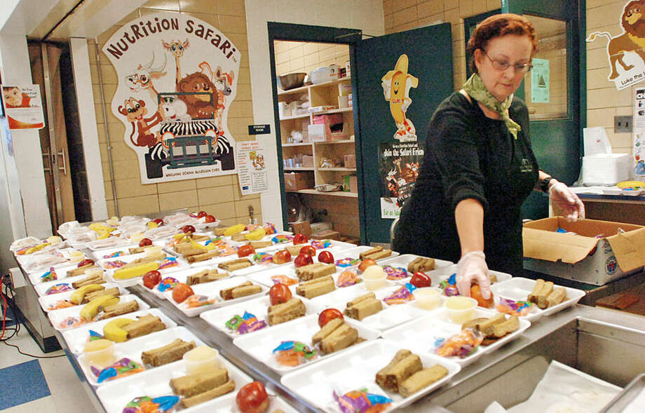 Hour file photo / Erik Trautmann Kendall Elementary School cafeteria staff prepare lunch trays for students.