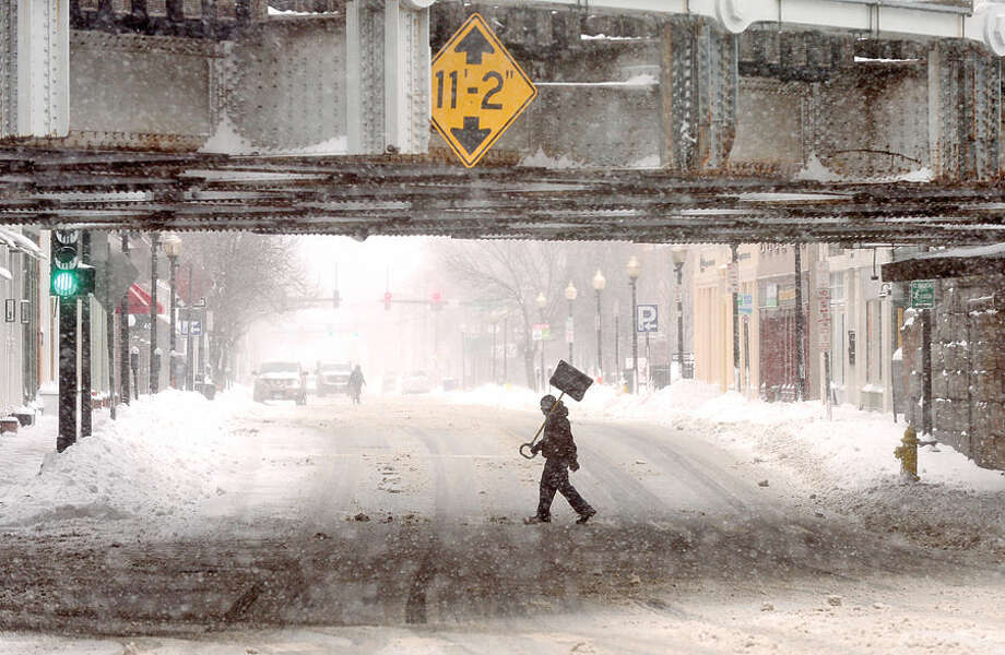 Hour photo / Erik Trautmann A pedestrian crosses South Main St as Norwalkers cope with the blizzard that hit the Northeast Tuesday.