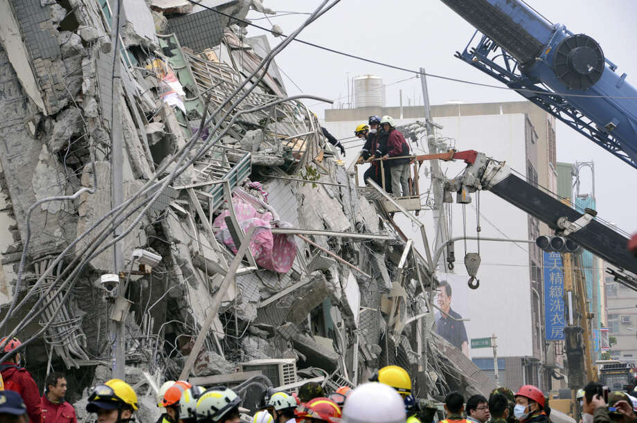 In this photo released by China's Xinhua News Agency, rescuers search for survivors at a quake site in Tainan, Taiwan Saturday, Feb. 6, 2016. A powerful, shallow earthquake struck southern Taiwan before dawn Saturday. (Zhang Guojun/Xinhua via AP) NO SALES