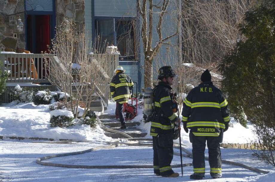 Hour Photo/Alex von Kleydorff Norwalk Firefighters enter a house on Red Oak lane as they respond to a chimney fire on Wednesday