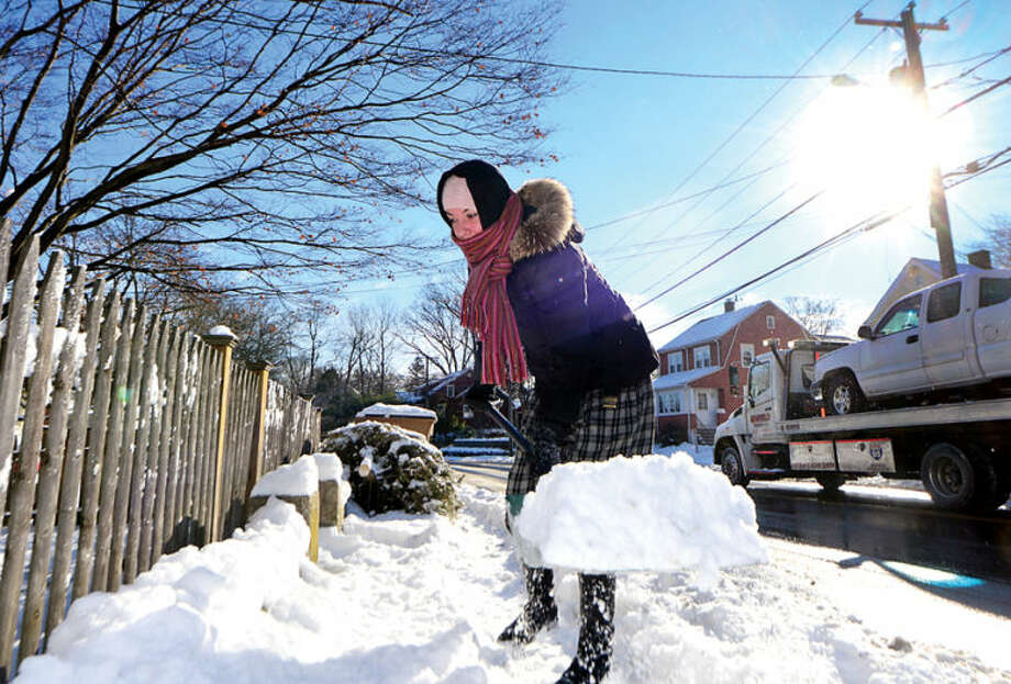 Danielle Habdas shovels the walk in front of her house in Stamford Wednesday morning following the snowstorm Tuesday that dumped several inches in the area.