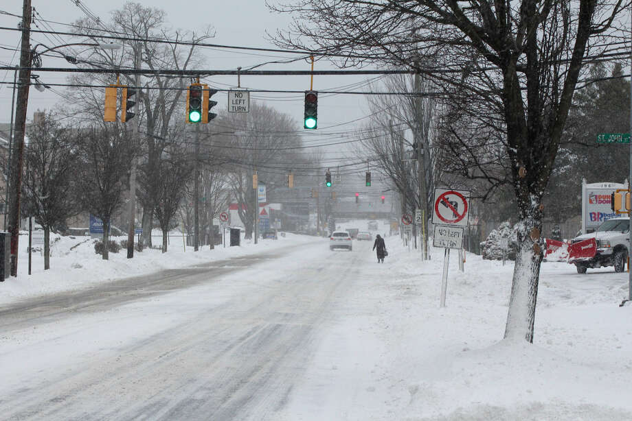 Hour photo/Chris BosakA pedestrian walks down East Avenue in Norwalk on Tuesday morning during the year's first blizzard.
