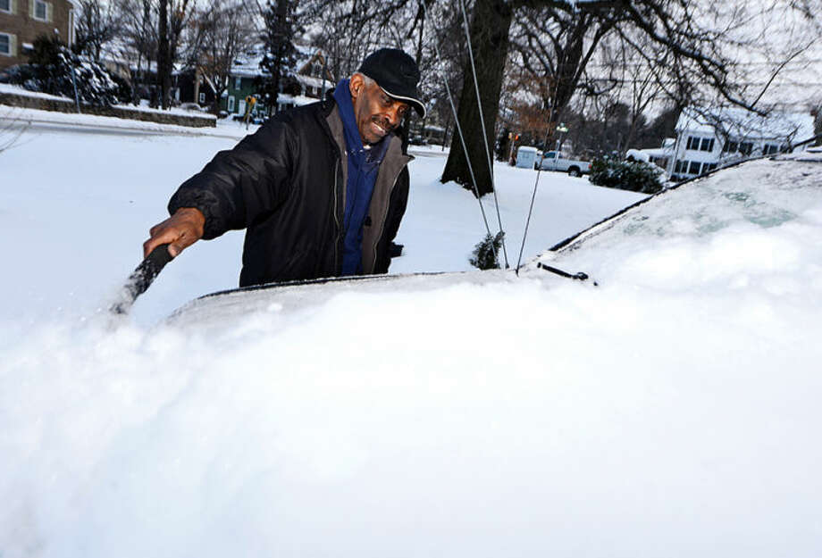 Jerry Evans cleans off his car on Adams Street Wednesday morning following the snowstorm Tuesday that dumped several inches in the area.