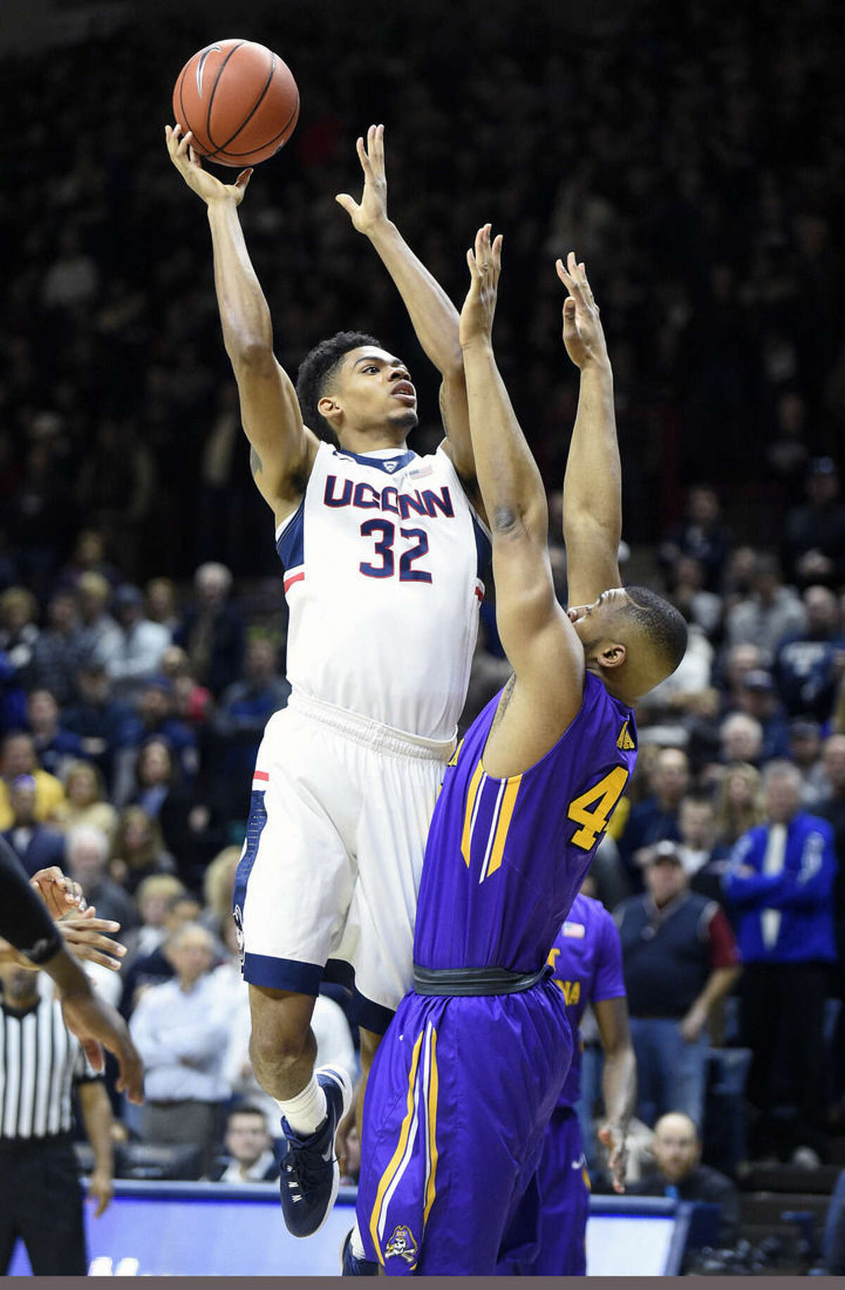 Connecticut's Shonn Miller (32) drives over East Carolina's Kanu Aja (44) during the first half of an NCAA college basketball game in Storrs, Conn., on Sunday, Feb. 7, 2016. (AP Photo/Fred Beckham)