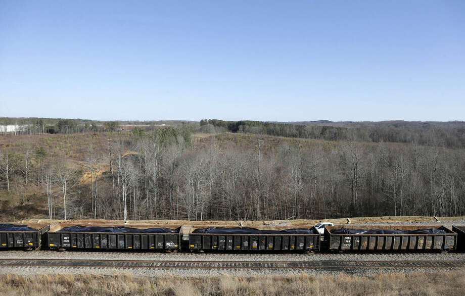 In this Thursday, Jan. 14, 2016, photo, rail cars filled with coal ash await transportation from the Dan River Steam Station in Eden, N.C. Duke Energy Corp. is digging up and hauling away the toxic coal residues two years after one of the worst coal-ash spills in U.S. history. (AP Photo/Gerry Broome)