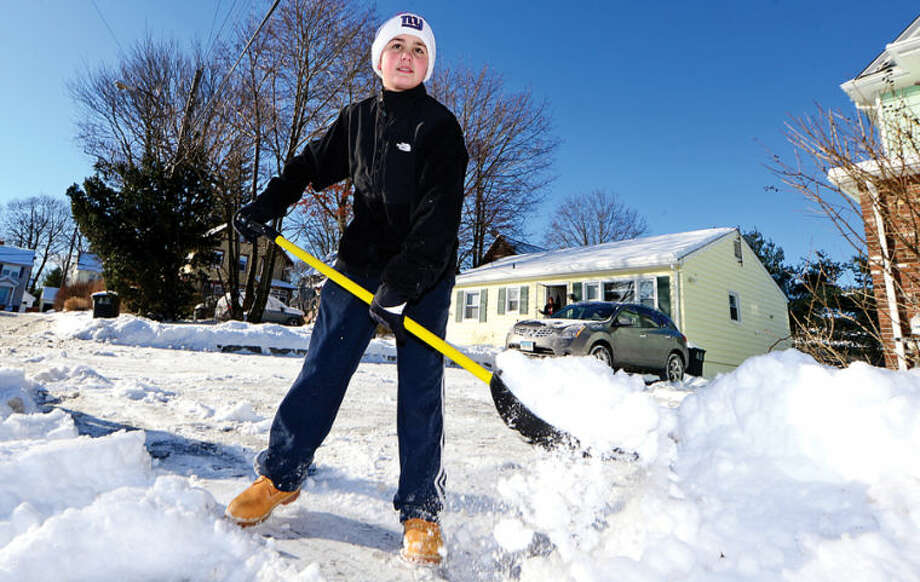 Matt Mailhot helps his neighbors by clearing snow from their driveways in Stamford Wednesday morning following the snowstorm Tuesday that dumped several inches in the area.