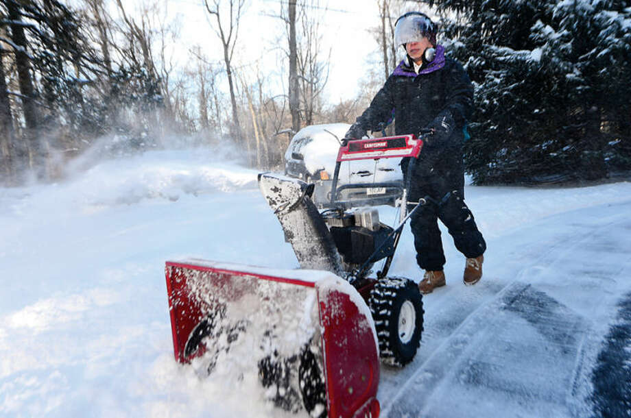 Stephen Chan uses a snowblower to clear his driveway in Wilton Wednesday morning following the snowstorm Tuesday that dumped several inches in the area.