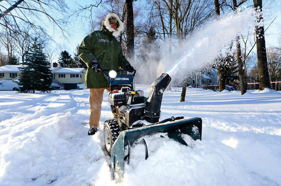 Mark Reifers uses a snowblower to clear his driveway on Ivy Lane in Wilton Wednesday morning following the snowstorm Tuesday that dumped several inches in the area.