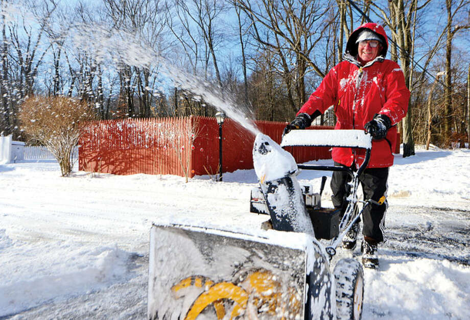 Cesar Ambruoso uses a snowblower to clear his driveway in Stamford Wednesday morning following the snowstorm Tuesday that dumped several inches in the area.
